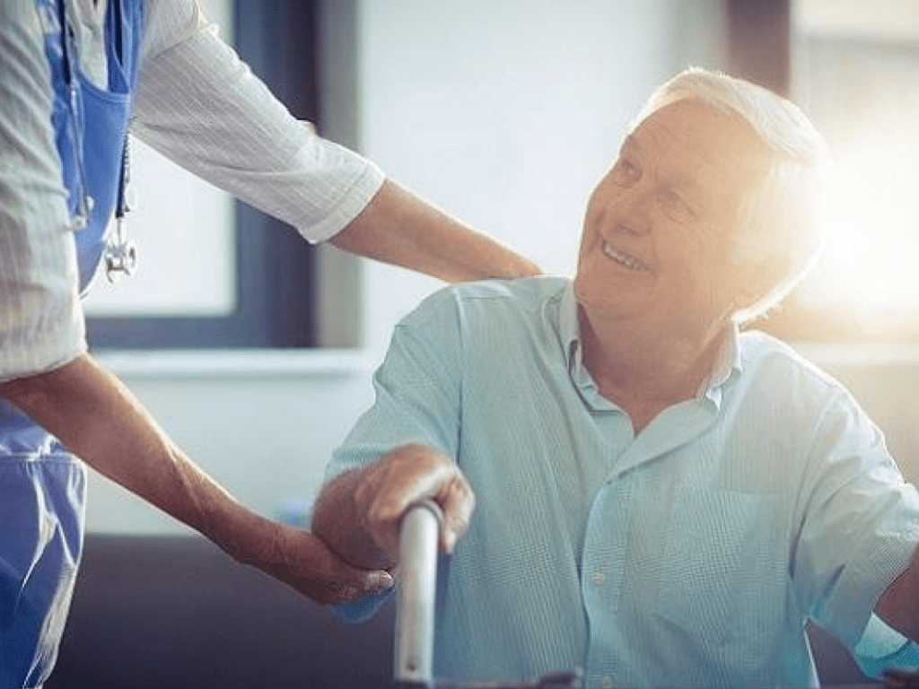 Professional aged care worker helping a senior male.